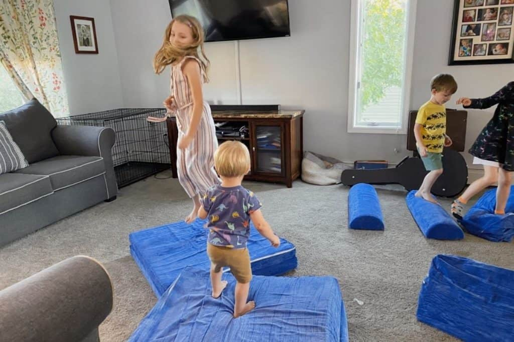 kids jumping on Brentwood home play couch pieces to help reshape them after unpacking