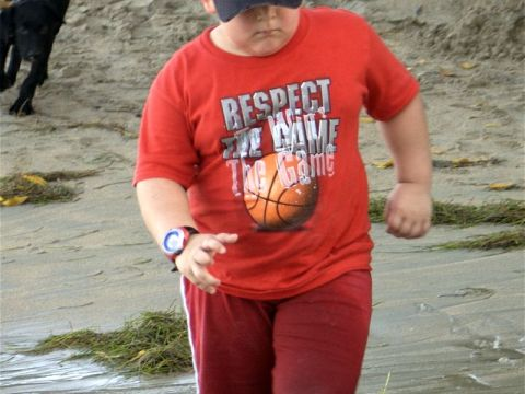 Overweight boy walking on beach
