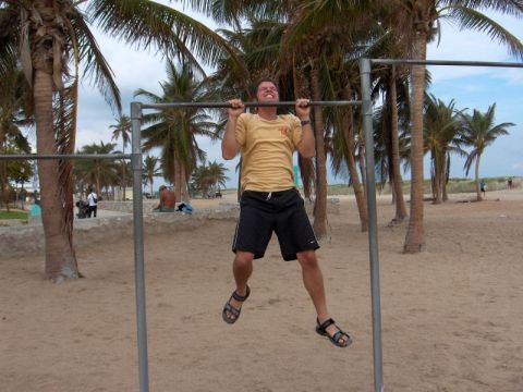 Man doing pull-ups on beach