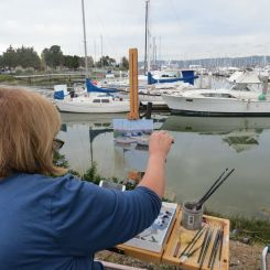 Local painters work together side by side, setting up easels at the park.