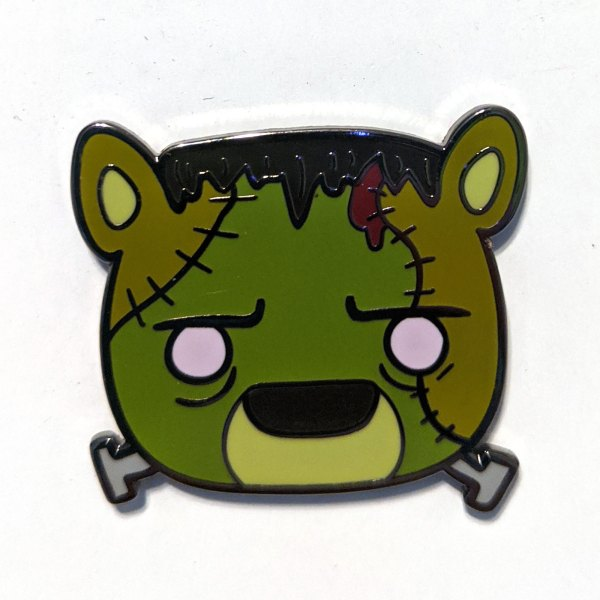 A photo of bearenstein's monster - an enamel pin of a cute bear version of frankenstein's monster