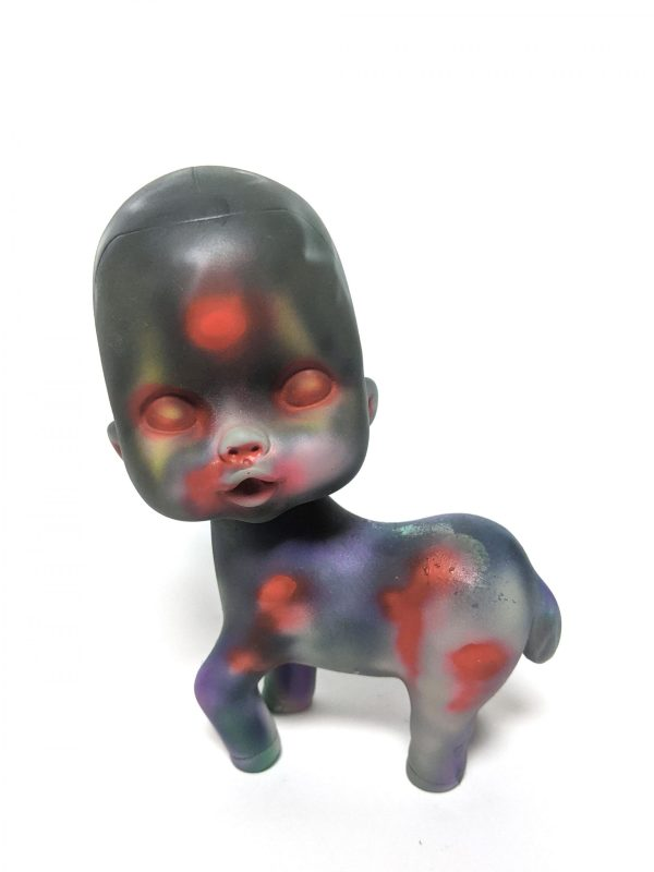 a wounded pony dripping blood with a baby head on it that has 3 eyes