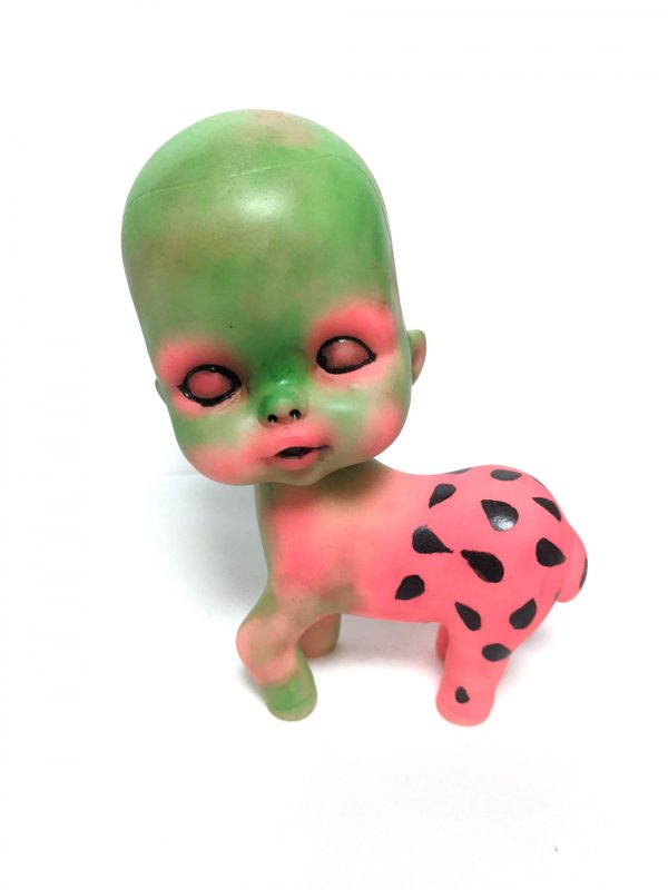a pony toy with a baby head painted green and pink with watermelon seeds on it