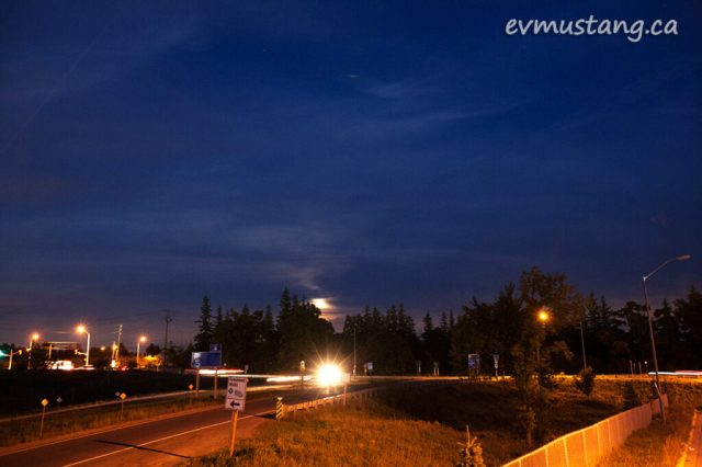 long exposure image of the turn off to milton from the 401 ontario highway with rising moon behind a tree