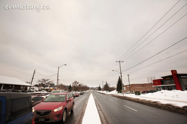 image of the northbound lanes of the parkway north of lansdowne street in peterborough showing cars waiting at the light coming toward the camera and an empty lane of wet pavement heading away