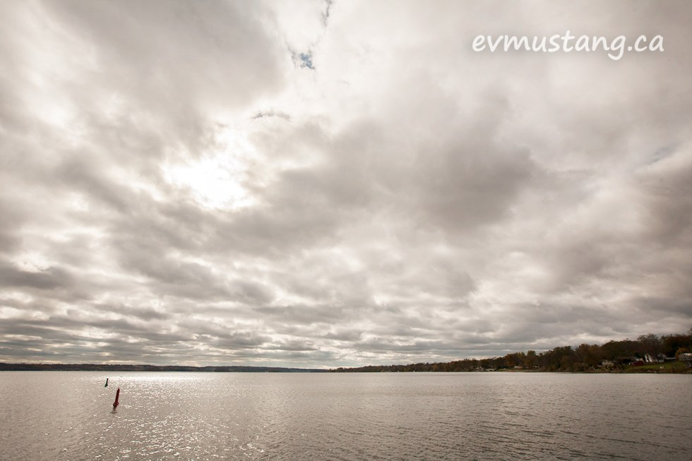 image of buoys in rice lake with a patch of sun breaking through the clouds creating reflections on the water