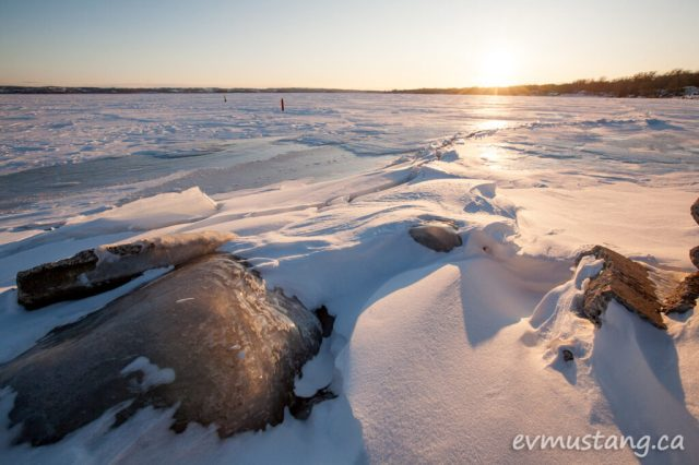 image of rocky shore coated in ice in the foreground with ice covered lake and sunset in distance