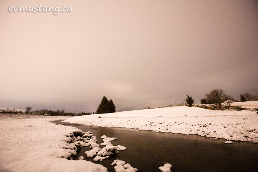 image of snow at night blanketing a farm field with a stream and a few trees