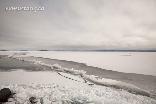 image of a jagged ice shelf pushed up through the surface of rice lake with open water and a buoy in the distance
