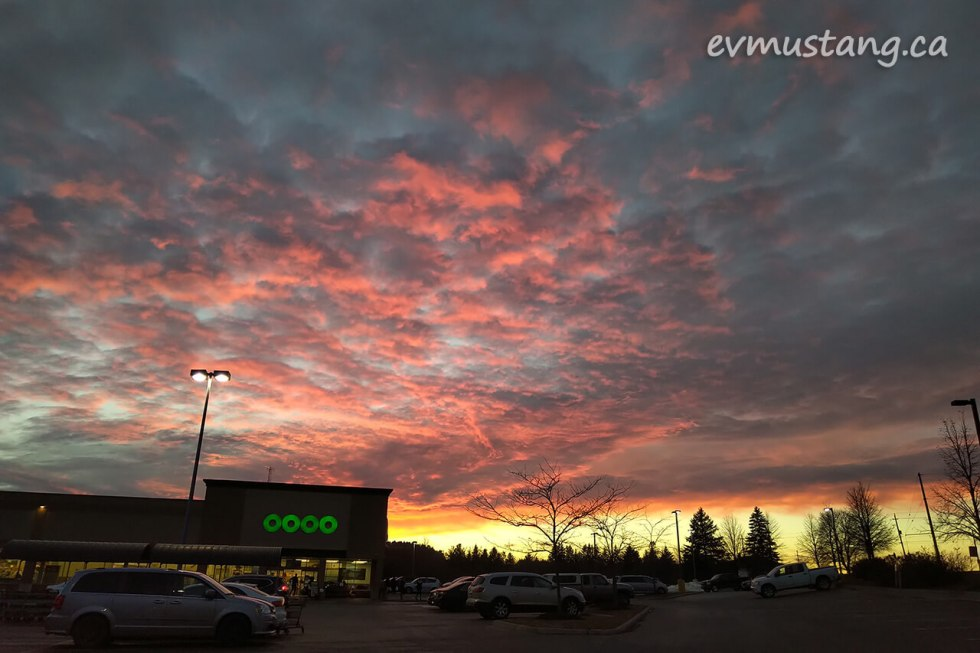 image of intense peach and plum sunset over suburban grocery store and parking lot
