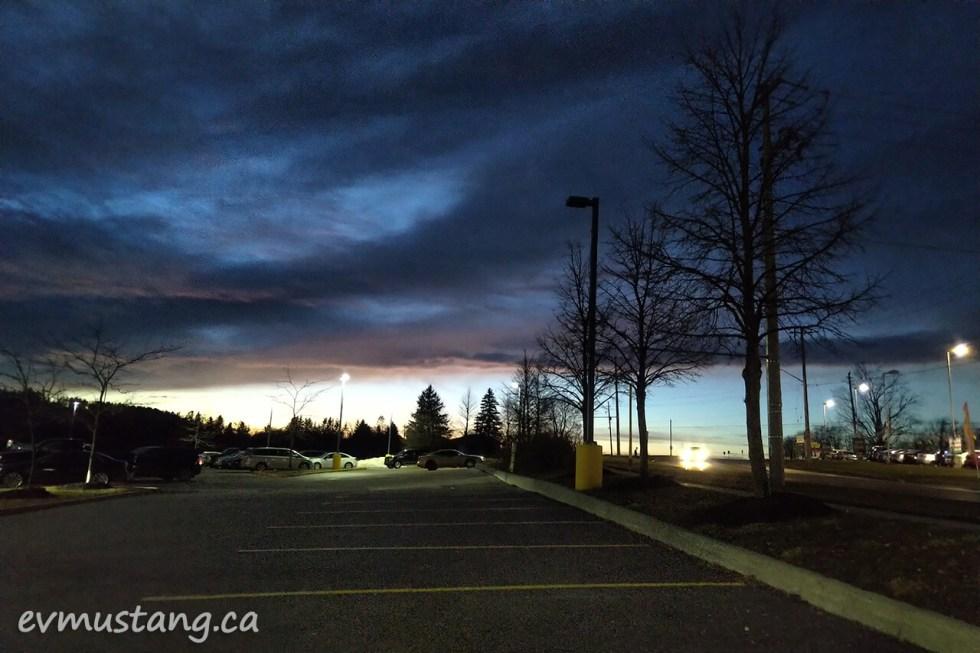 image of intense dark plum sunset over suburban parking lot at twilight