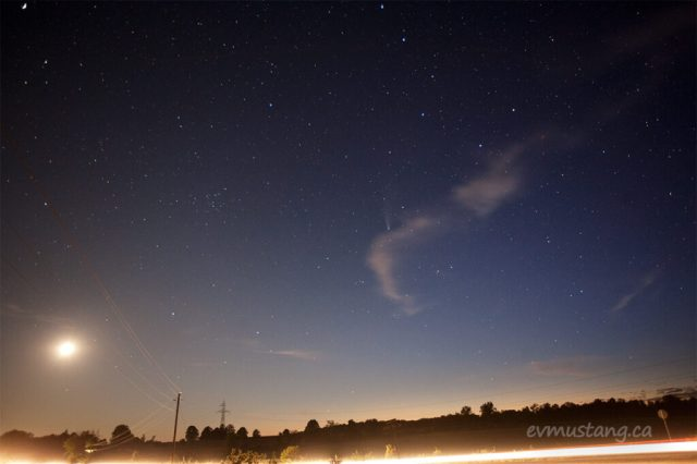 image of comet c/2020 july 24, 2020 over douro, ontario just before nautical twilight with the tail lights of a truck going by underneath and a smudge of a crescent, setting moon