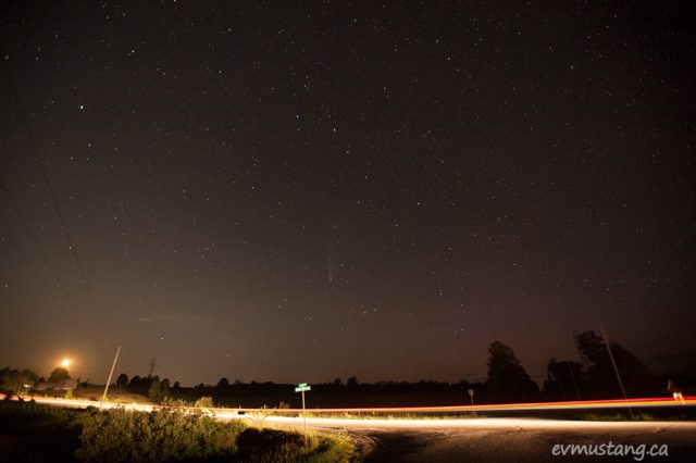 image of comet c/2929 f3 neowise in a dark sky over the light trails from several head and tail lights that show the roadside landscape, the moon is disappearing behind the treeline.