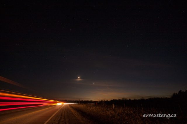 a photograph of the pairing of jupiter and saturn close to the new moon with the last glow of the sunset in the west. in the foreground is a roadway with the streaking tail lights from vehicles passing through. it is a long exposure, so the lights leave long amber and orange lines across the image.