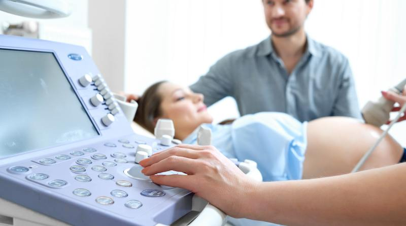 Young loving pregnant couple visiting doctor together