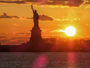 statue of liberty against a setting sun