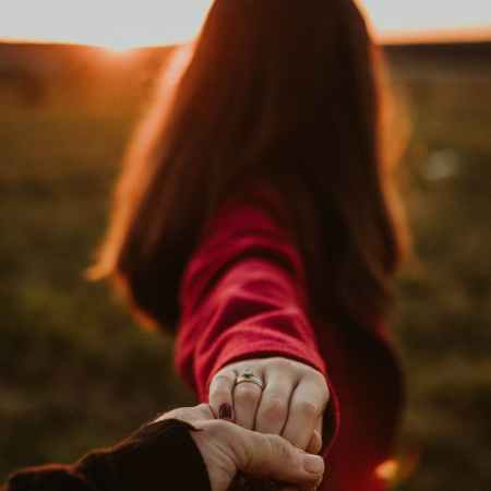 couple holding hands in sunny field