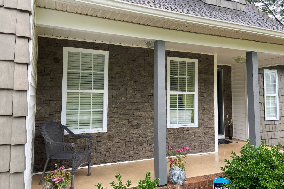 brown mortarless stone veneer on front pation of home with two white windows