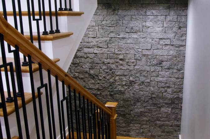grey interior stone veneer accent wall on staircase
