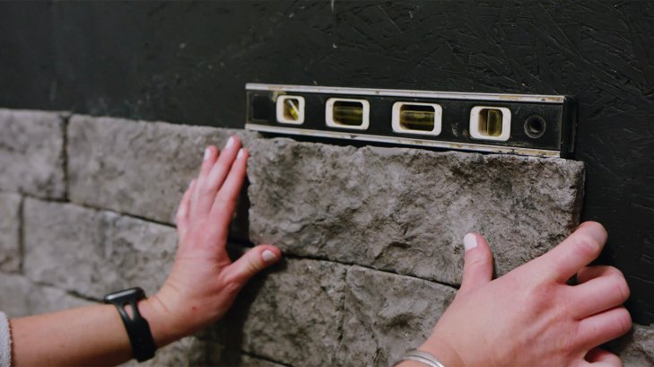close up of level above grey stone as person adjusts the veneer with their hands