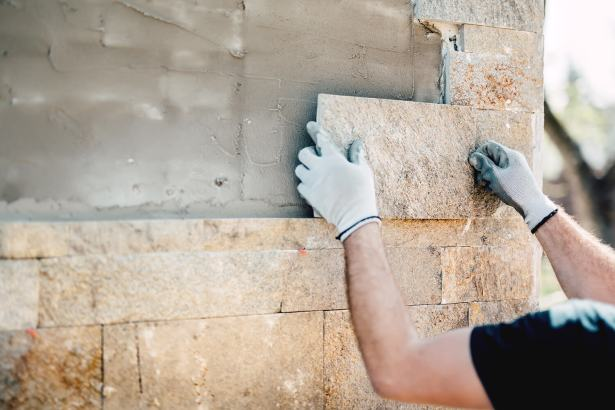 close up of man wearing white gloves and placing tan tradition stone veneer on exterior of house