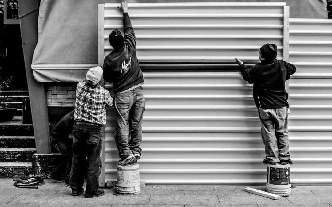Three men working on construction job in awkward positions.