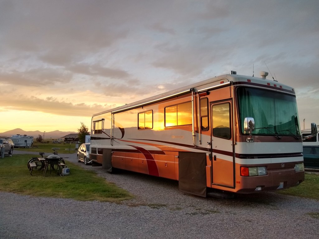 Evolving Escapades RV and tow car in a campsite with the sunset reflection on the side of the RV along with the mountains in the background as we travel the country as nomads.