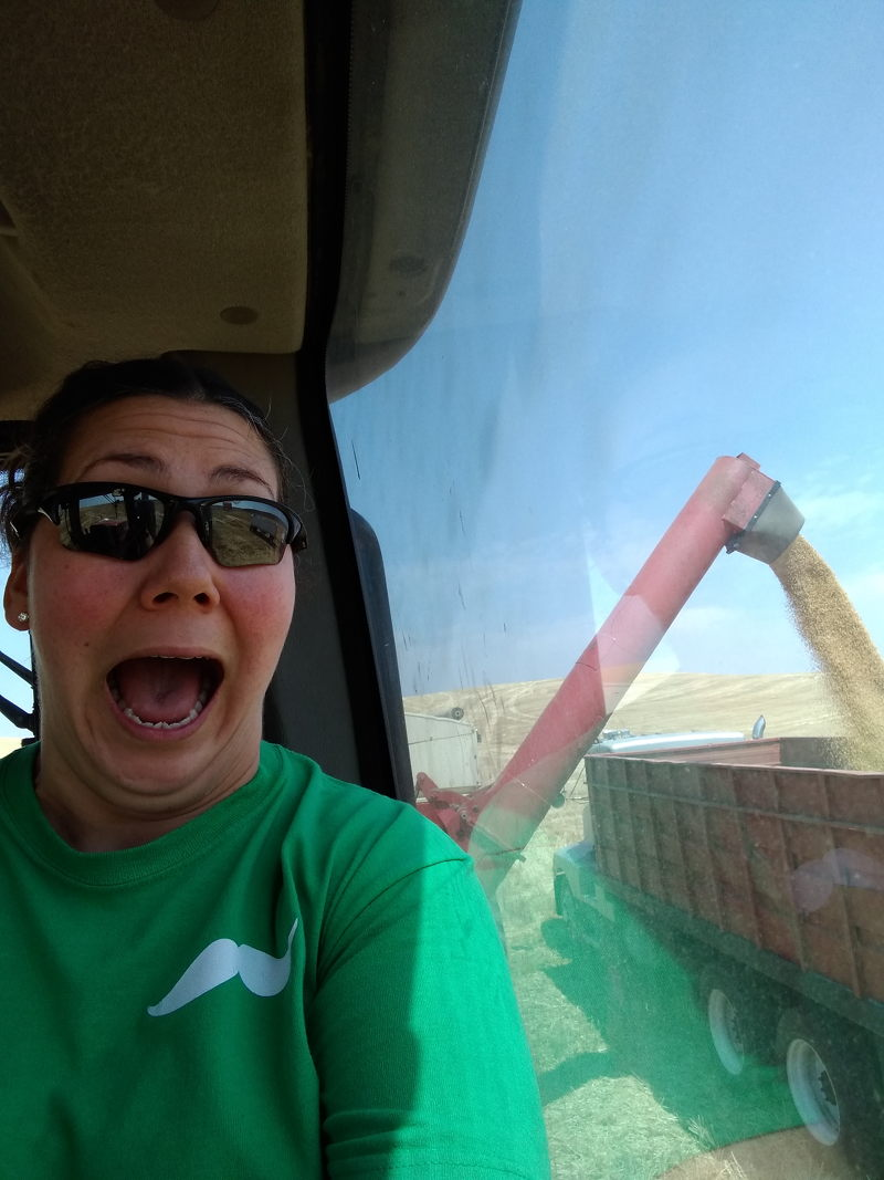 Adrianne taking a selfie from inside the bank out wagon while dumping grain into the truck in the background while traveling the country full time in our RV.