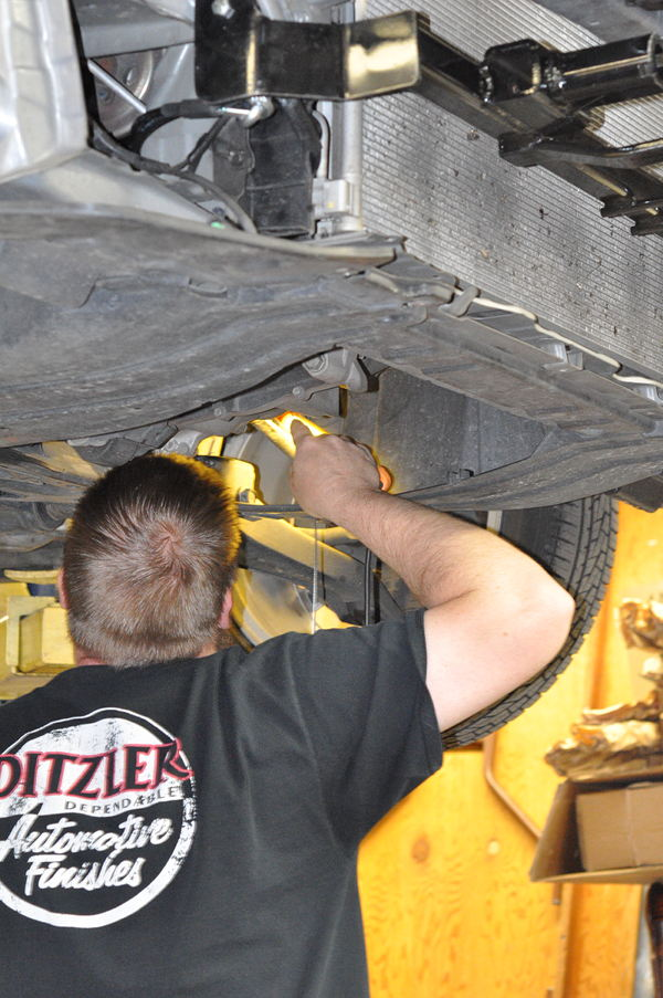 Adam shining a light into the engine compartment from underneath the car trying to feed the Ready Brake cables through the firewall while setting up the RV tow car to travel the country.