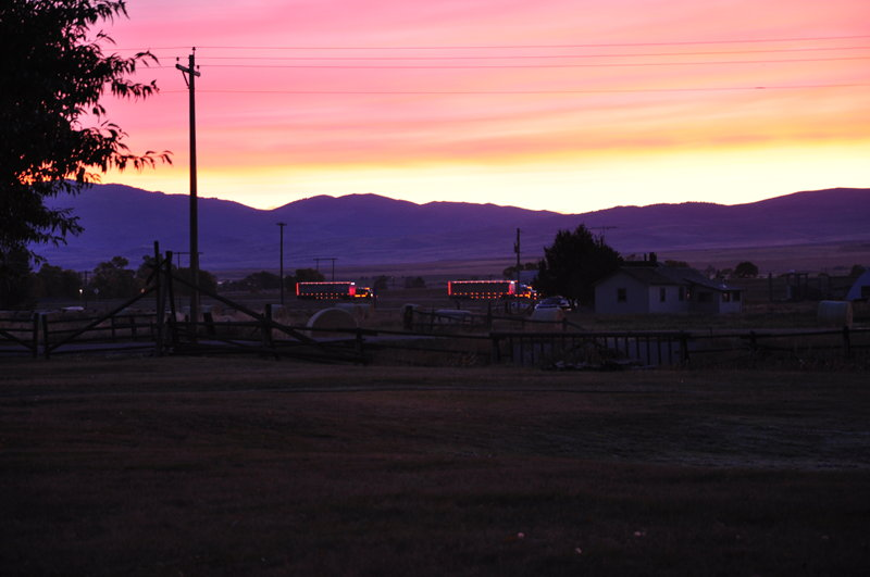 A couple semi's with all the cargo lights on driving along the freeway at sunrise with the mountains in the background as we sit in our campground while living full time in our RV.
