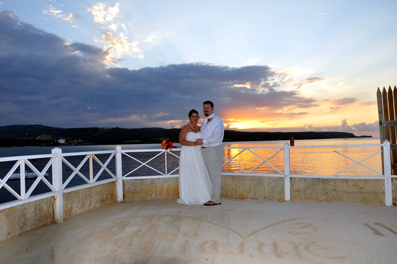 Adam and Adrianne posing for a wedding picture at sunset in Discovery bay Jamaica.