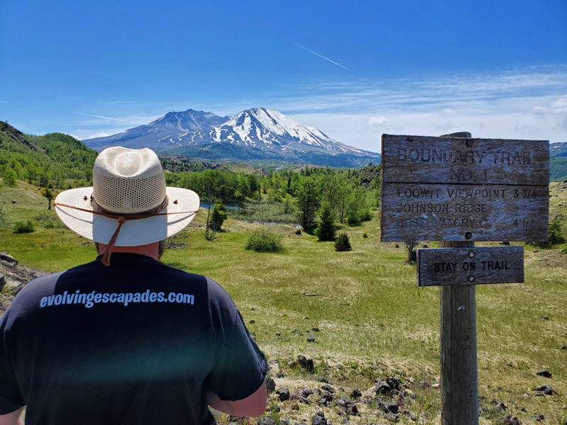 Adam standing next to the Boundary trail sign with Mt St. Helens in the background.
