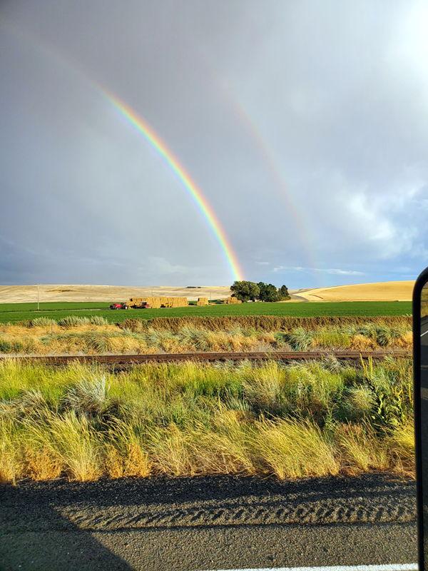 A double rainbow that ends near the farm house.