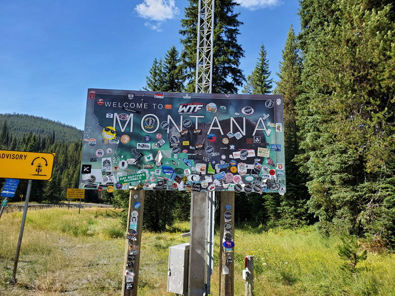 Welcome to Montana sign at the state border with random stickers all over it.