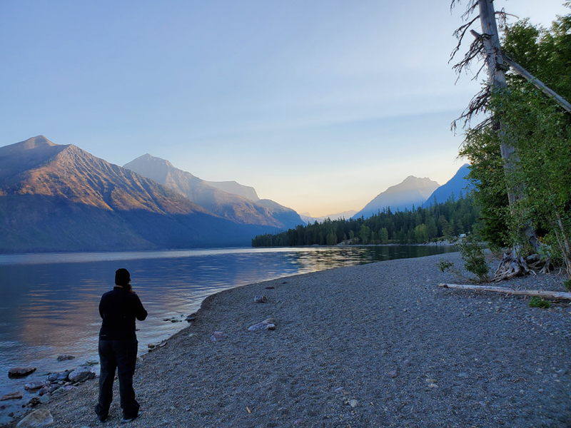 Adrianne taking a picture of Lake McDonald at sunrise from the shoreline of the lake.