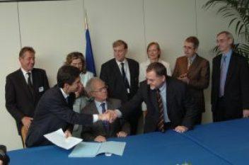 """През 2004 г. управляващият директор на """"Филип Морис Интернешънъл"""" Андре Каланцопулос (вляво) и Михаеле Шрейер, еврокомисар по бюджетните въпроси (вдясно) си стискат ръцете и поставят началото на 12-годишно споразумение за борба с незаконната търговия на тютюневи изделия. Фото: Европейска комисия"""