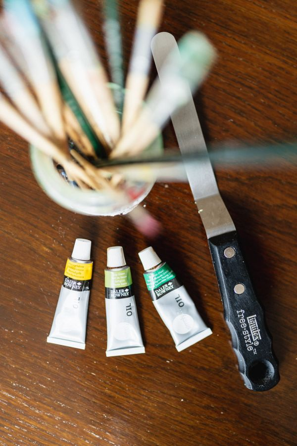Photo taken from above that shows a jar of assorted paint brushes, three tubes of paint, a painter's spatula - al arranged on a dark wood table.