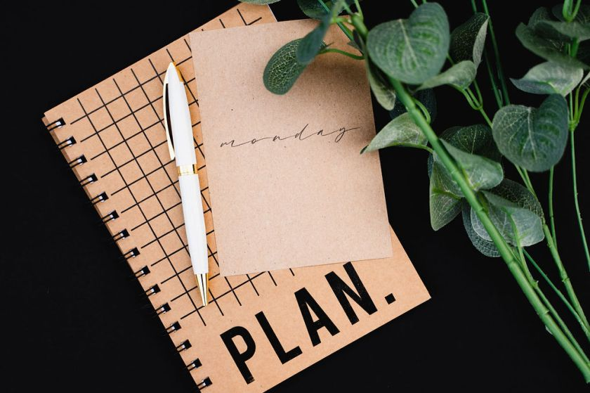 On a black background, a brown spiral-bound planner with a black grid and the word PLAN. in printed in black at the bottom. On top of the planner is brown paper card with Monday written on it and a white and gold pen. Over the upper right corner are the green leafy stems of a flower.