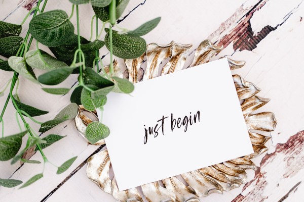 White card that says Just Begin in the middle. The card is lying on top of a gold leaf-shaped plate which is on a weathered wooden table with some greenery at the top of the photo.