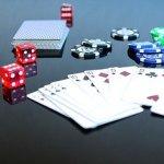 Cartes, dés et jetons de casino sur une table.