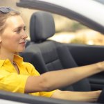 Image of a happy woman driving a convertible - understanding emotional drivers help influence behaviour and perception