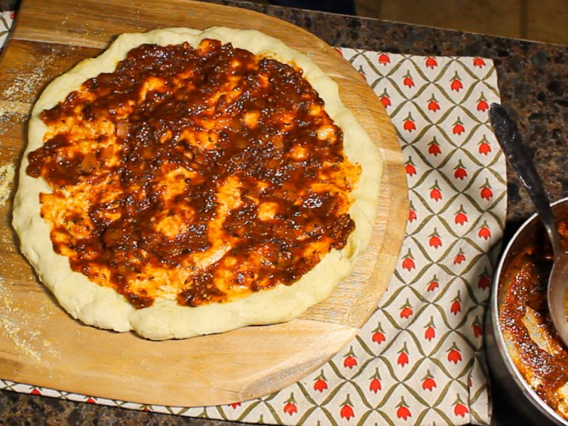 Thick red pizza sauce spread onto an unbaked pizza crust