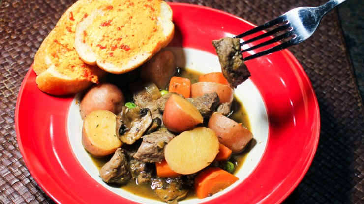 Stew in a bowl with big bites of beef tenderloin, red potatoes, carrots, mushrooms, peas, and broth with red-pepper buttered bread on the side