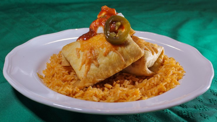 Two chimichangas on top of red rice topped with sour cream, salsa, and a jalapeno