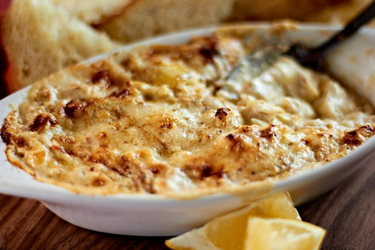 Crab and artichoke dip baked until golden brown served with bread and lemon