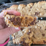 Lactation Cookie Bar held in front of the pan with the rest of the peanut butter chocolate chip lactation bars