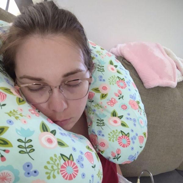 Mom sleeping and pumping using a Boppy as a pillow