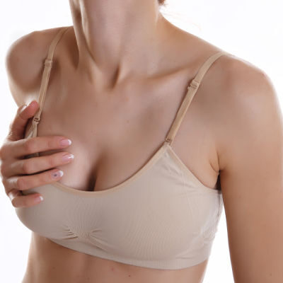 woman wearing nude bra and holding bra as if in pain