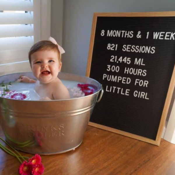 Pumping photoshoot: Baby in a milk bath with a letterboard listing how much and how long mom pumped