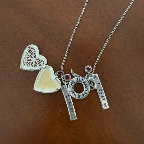 Breastmilk locket necklace in a heart shape with the names Cooper and Landon engraved on a brown table background
